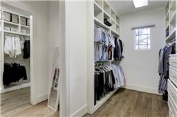 "[Master Closet]An over-sized ""U""-shaped, walk-in  closet offers abundant custom-fitted storage. Note window and abundant natural light,."