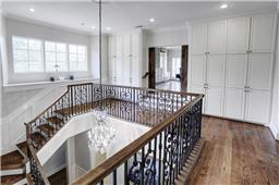 [Main Staircase Landing]The main staircase landing offers a wall of storage cabinets and expands into a spacious gameroom. Note custom iron balustrade.