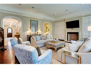 Large living area off entrance gallery is open to the kitchen and casual dining area.  The playroom is through the archway on the right.