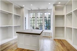 Light filled and thoughtfully designed master closet with crystal pendants, packing island and glass dressing table.