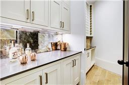 Antique mirrored butler pantry leads into the separate wine room.
