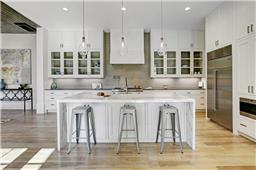 Tile back splash by Ann Sacks carries up into glass front cabinets for a unique, crisp look. Waterfall edge island with bar seating.