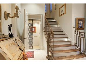 Stairs to the second floor and entry to the paneled elevator, which services all three floors.
