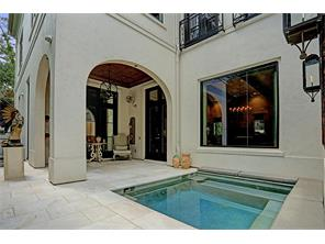 Arched outdoor loggia  and spa/pool with built-in bench seating. The living room, breakfast area, and kitchen enjoy views of this area, as does the master study on the second floor and the third guest bedroom on the third floor.