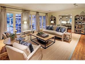 Banks of French windows employ a great view of the impeccable grounds graced by the resort style patio & pool. Custom drapes, multi-piece molding & hardwoods enhance this stunning family room.  There are pocket doors to close off from kitchen area.