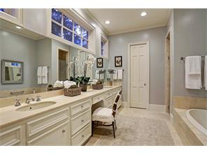 Master bath is replete with travertine marble floors, marble counters with double sinks, a vanity, garden tub, walk-in shower with bench seat, wall of built-ins & enclosed water closet.  Clerestory windows are a great touch affording natural light.