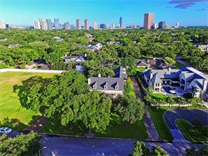 Aerial view highlighting the density of lush greenery affording the property and wonderful central location. Note downtown Houston in the background. This location has easy access to most work corridors and many nearby neighborhood conveniences.
