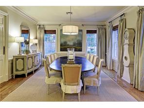 Stately dining room takes elegance to a new level.  Multi-piece molding, wainscoting, hardwood floors, decorative four light chandelier, and magnificent custom drapes complete the room. There is a privacy door to the kitchen and a nearby wine closet.