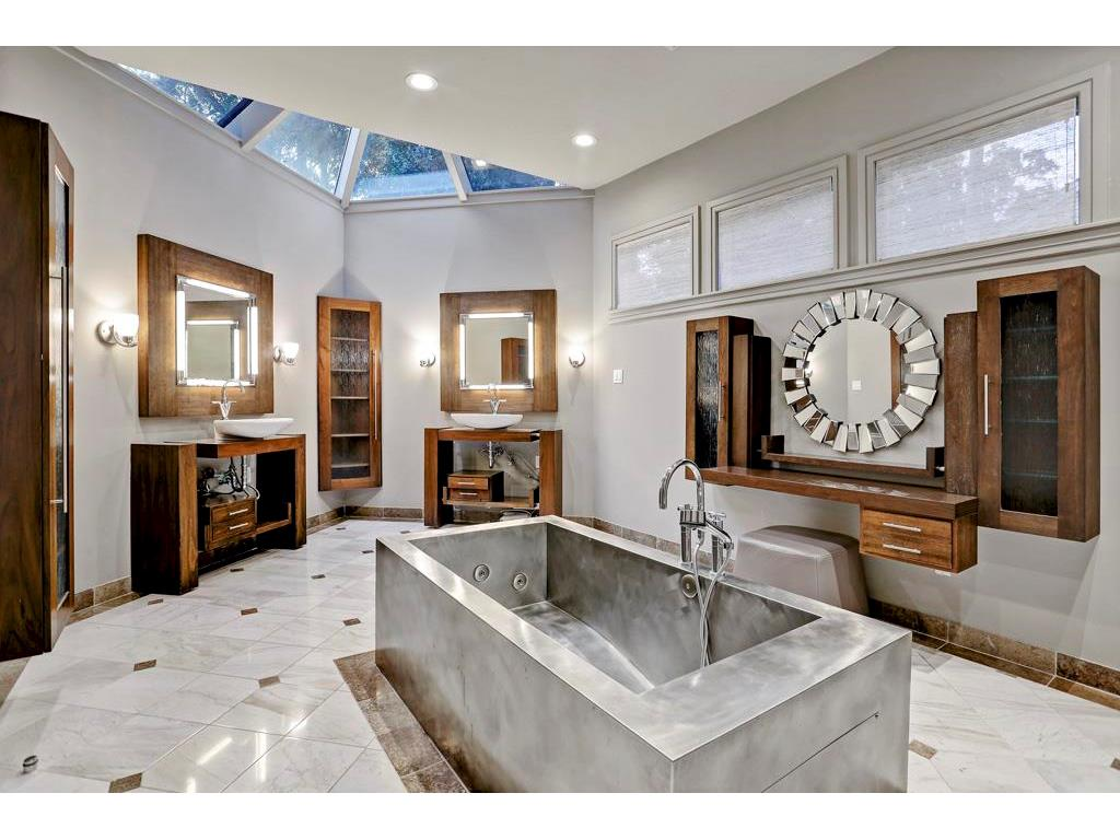 The luscious bath has marble flooring, custom free standing soaking tub, dual sinks, make-up vanity, steam shower and a skylight bestowing streams of natural light.