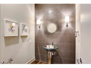 Gorgeous Powder Bathroom embellished with a custom floor to ceiling tile accent wall, sunburst mirror, wall mounted sconces and modern pedestal sink.