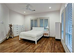 Additional Secondary Bedroom with plantation shutters, hardwood flooring, recessed lighting and a spacious walk-in closet with built-ins. Shared Hollywood Bathroom.