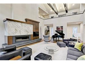 A custom gas ribbon flame fireplace with modern wood paneling & stone mantel and hearth serves as the centerpiece. Open gallery to the second floor.