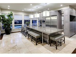 Chef s kitchen with a massive quartz-clad island offering seating on two sides, commercial grade SS Viking double refrigerator, Bosch dishwasher, Wolf 5-burner gas cooktop & Thermador double oven, multi tiered storage.