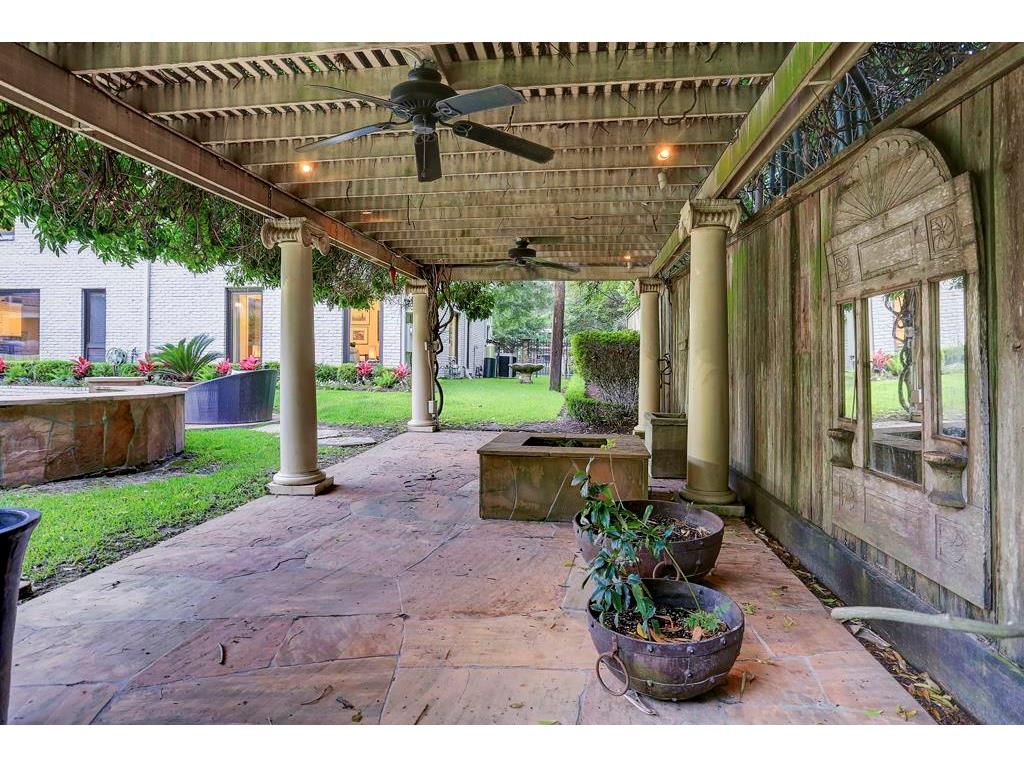 Wisteria covered pergola covers a stone patio with fire pit