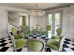 Empowered by an exquisite chandelier, the dining room seamlessly transitions with  the  entry hall and  living room.  View of circular drive.