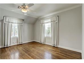 Well-appointed bedroom with gleaming hardwoods, custom draperies, crown molding and walk-in closet.