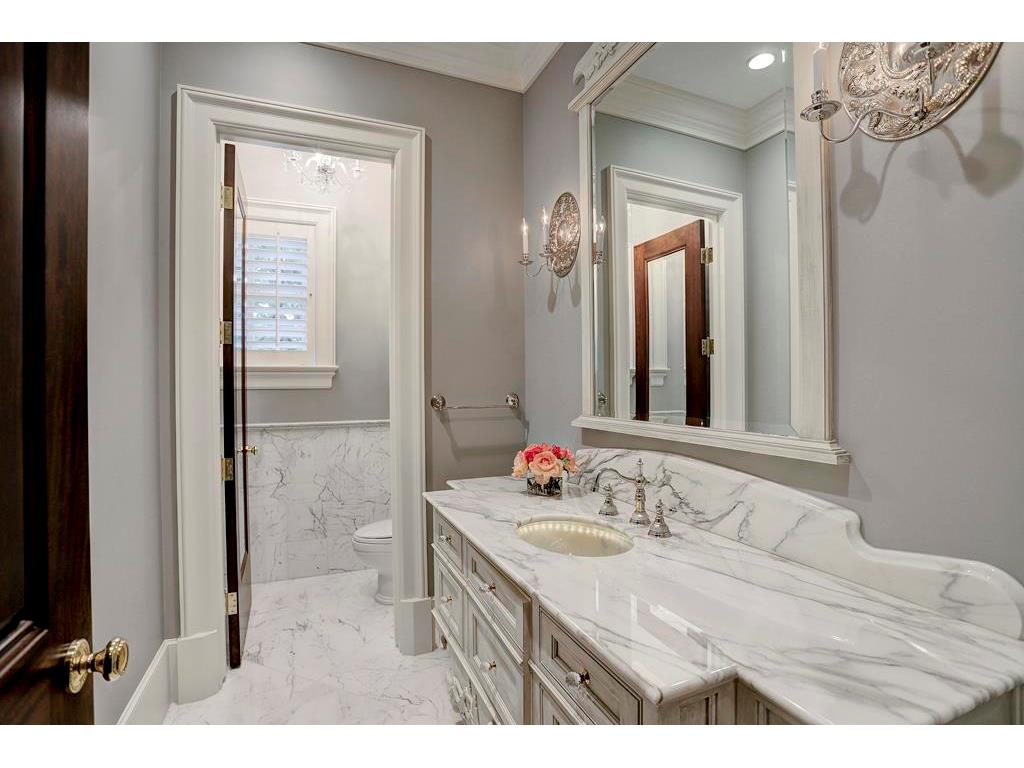 The POWDER BATH has marble floors and wainscoting (in the commode room), a marble-topped vanity with an etched lighted glass sink, and a built-in framed beveled mirror.  This room is gorgeous!