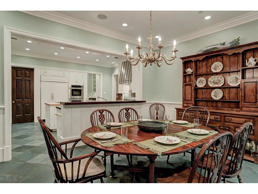 The BREAKFAST ROOM is generously sized and can accommodate a large table & breakfront.  Notice the double crown moldings, the brass chandelier & the bar that is shared with the Kitchen.
