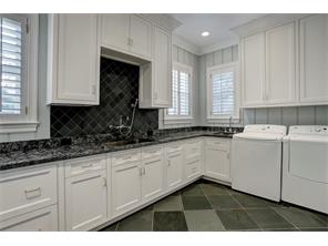 1ST FLOOR LAUNDRY ROOM has windows for natural lighting, shiplap on the walls, granite counters, a slate floor & backsplash above the large washing sink, a large closet for cleaning implements, & a ton of storage cabinets.  There are 2 sinks!