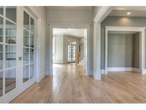 This photo captures the open feel throughout the home. Solid wide-boardwhite oak flooring. Pocket doors render privacy to the study on the left. Customwoodwork throughout the home is from Madera Works of Texas.