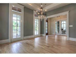 Elegant dining room opens to entry. Coffered ceiling, multi-piece molding,windows graced by transoms.