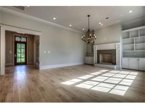 Spacious family room with fireplace flanked by bookcases opens to thekitchen affording perfect flow for entertaining.