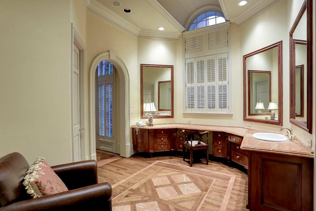 The second MASTER BATH - this one with glass front walk-in shower (bench/shower head/wand), vanity station with marble counter top, hardwood flooring with marble insets, plantation shuttered windows, walk-in closet (storage and dressing stations).