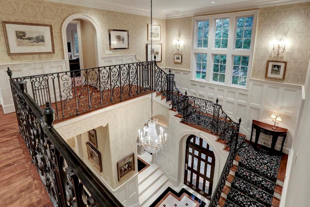 The stately STAIRCASE to the SECOND FLOOR HALLWAY is beautifully accented against the hardwood flooring, stenciled walls, crown/base molding, painted wainscoting. The corridor is brightly lit by natural light from the mullioned windows.