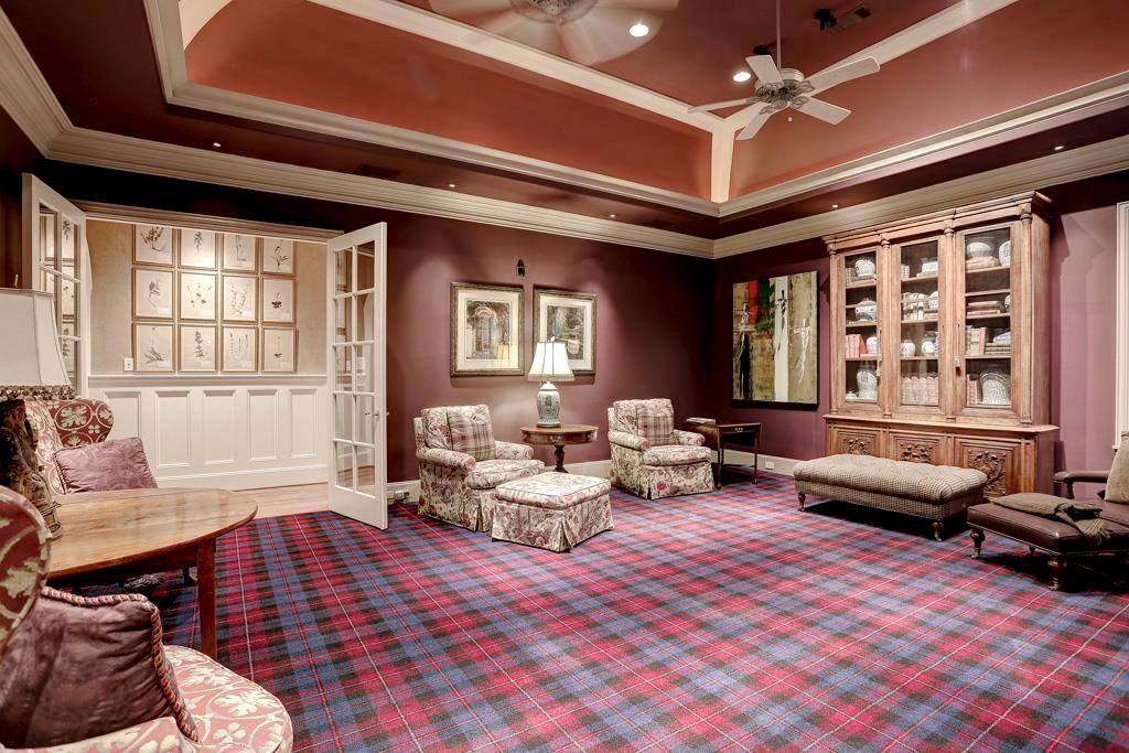 The second floor MEDIA ROOM (23X20)  includes a built-in wood  entertainment center, raised Mansard ceiling with wood accents, cove lighting, carpeted flooring, plantation shutters and wet bar (granite counter top/back splash, sink, cabinets).