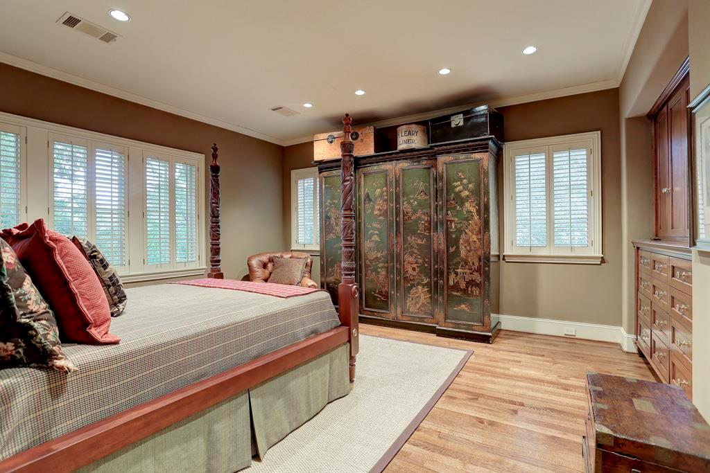 One of four upstairs BEDROOMS - this one (17X16) features built-in wood cabinets/drawers, walk-in closet with shelving, plantation shuttered windows, hardwood flooring, recessed lighting and en suite bath.
