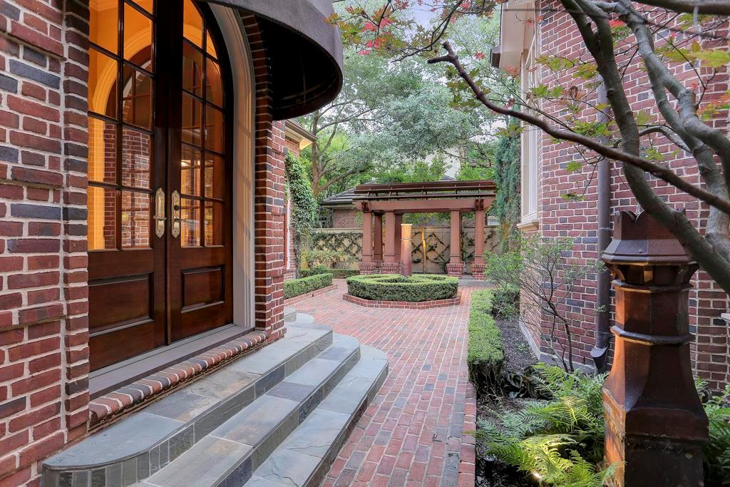 Exquisitely crafted French doors  from the Living Room open to the back yard with its brick paved flooring, wood stained pergola and finely manicured shrubs /greenery.