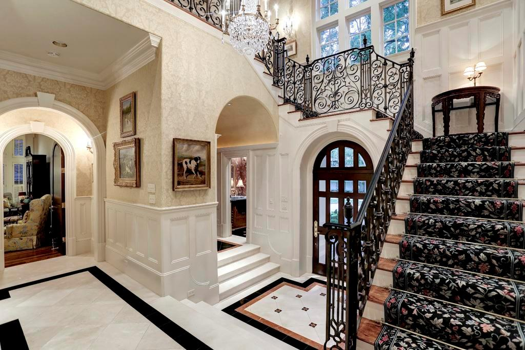 The gracious 2 story FRONT FOYER features an arched wood/glass entry door, grand staircase (decorative wrought iron railing), marble tile floor (decorative insets), crystal chandelier, double door coat closet, stairway to Powder Room and Library.