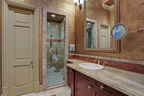 One of two Master Baths - this one features etched glass front walk-in shower (marble surround/shower head/wand), marble counter top/back splash, sky light, tile flooring, linen closet, separate water closet and walk-in clothing closet.