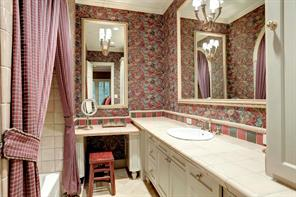 One of four upstairs BATHROOMS - this one features papered walls, tub/shower with tile surround, tile flooring, tile counter top with decorative back splash, vanity, framed mirror and decorative light sconce.