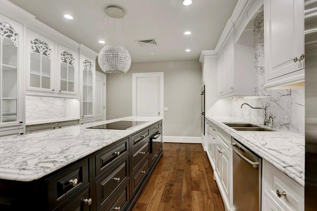 Elegant yet functional chef kitchen, w/ Calcutta Gold marble slab counter & back-splash.  Under-counter lighting, electric outlets under cabinets The cook-top is a induction cook-top, note the chandelier above is a vent-hood that doubles as a light.