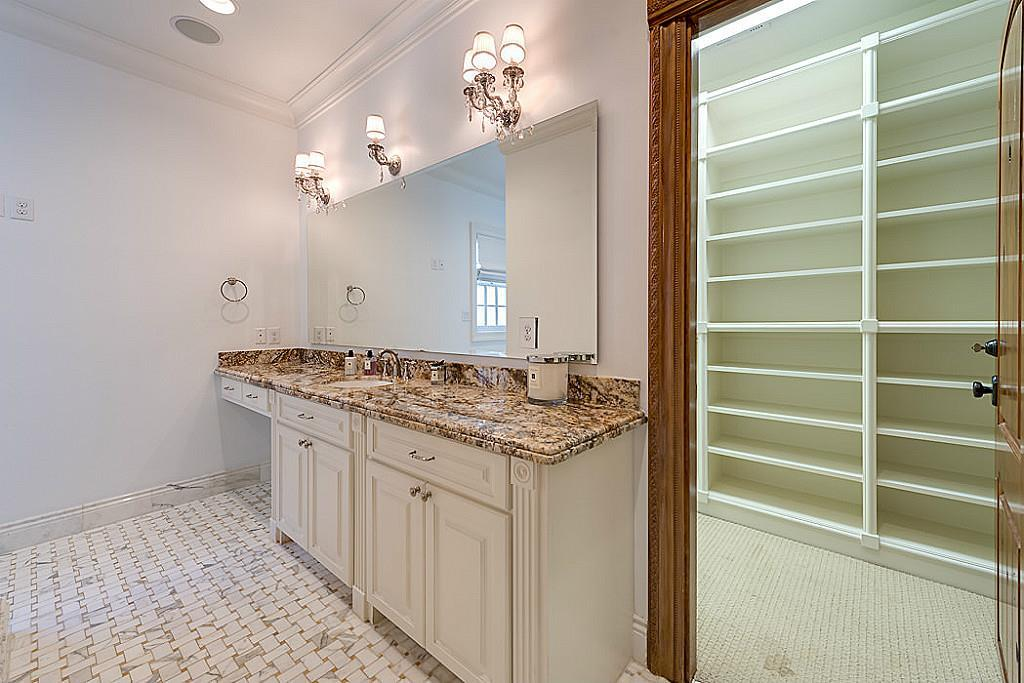 """[Master Bathroom #1]This luxurious master bathroom offers a sink and vanity cabinet with a beveled granite deck; an air tub; water closet with bidet; and a """"U""""-shaped custom-fitted walk-in closet."""