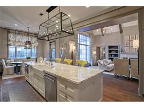 Another look at the easy FLOW between the Chef s Island Kitchen and the Family Room.  Notice the beautiful sconces on either side of the framed opening between the rooms and the wide farm sink in the Kitchen island.