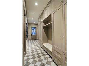 The MUD ROOM is conveniently located just inside of the 3-Car Garage and has marble floors, plenty of storage cabinets & drawers, and a wide bench for changing shoes.