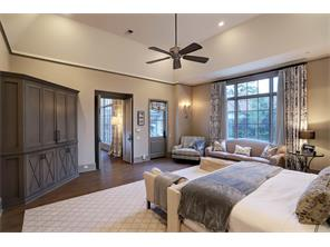 The 1ST FLOOR MASTER SUITE is off of the Family Room and has a private door out to the sumptuous Backyard.  Notice the raised ceiling w/fan and recessed lights, the floors to ceiling windows overlooking the pool, and those lovely French oak floors.