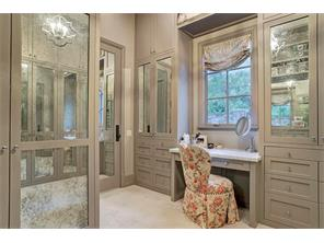 One of the two customized MASTER CLOSETS has a built-in dressing table, and antique mirror-fronted wardrobe cabinets.