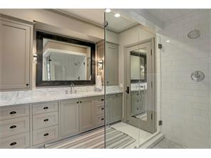 The EN-SUITE BATH for the previous Secondary Bedroom has a large walk-in shower with a Subway tile surround, marble floor and frameless glass door entry.  The built-in cabinets have a Carrera marble top and tons of storage!
