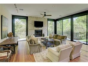 Family Room with 10ft. floor-to-ceiling windows on two sides and Texas limestone wall with a wood-burning fireplace.