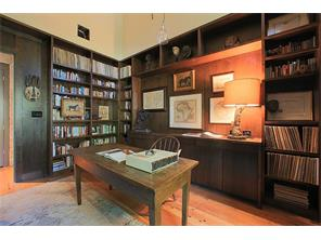The Study, located off the Living Room, has walls of built-in bookshelves and cabinets and vaulted ceilings.