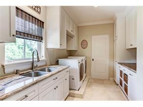Fantastic upstairs laundry room with unthinkable amount of custom storage! A delightful craft/hobby room is perfect for wrapping presents and all kinds of crafts adjoins this room.