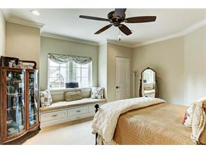 Bedroom with window seat, crown molding and ceiling fan.