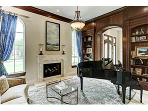 Impressively proportioned, the living room is complimented by Versailles pattern flooring, limestone fireplace, mahogany multi-piece molding and rich block paneling bookcases flanking the arched opening that unites with the entry.