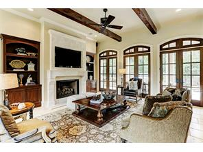 Banks of windows engulf the family room that encompasses a massive fireplace framed by mahogany bookcases.This room is resplendent with light and enjoys views of the spectacular grounds, pool and spa.