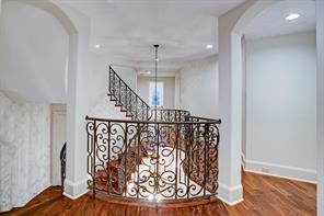 Upstairs landing with wide plank wood floors and fabulous iron designed railing.