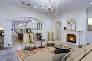 The family room has limestone floors, Italian marble fireplace with herringbone firebox is open to the gourmet kitchen and french doors to gardens.