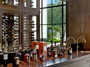 An oenophiles dream - a 700 Bottle glass and walnut storage wall and wine bar. Climate controlled through the home s sophisticated Savant system.